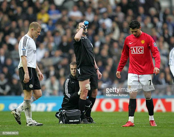 Referee Phil Dowd receives treatment on his right leg after pulling his hamstring before having to leave the field with his injury