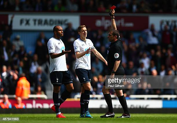 Referee Phil Dowd shows the red card to Younes Kaboul of Spurs as Michael Dawson of Spurs protests during the Barclays Premier League match between...