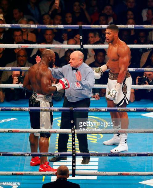 Referee Phil Edwards asks Cameroonborn Carlos Takam if he wants to stop the fight after receiving a cut against Britain's Anthony Joshua during their...