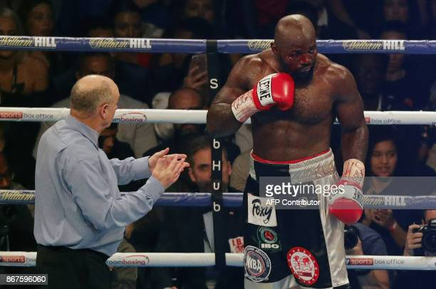 Referee Phil Edwards takes measure of a badly cut Cameroonborn Carlos Takam during his world heavyweight title challenge against Britain's Anthony...