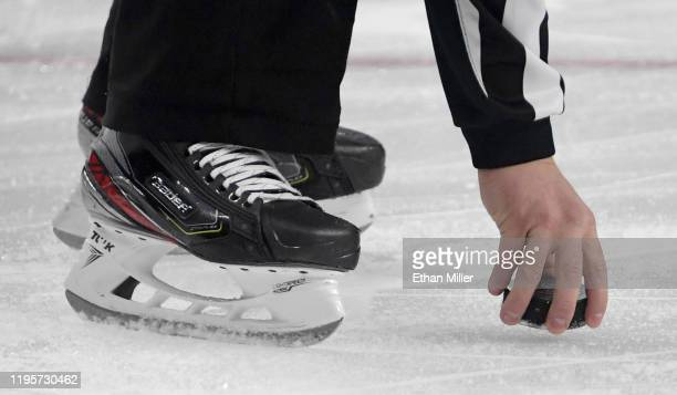 Referee picks a puck up from the ice during a game between the Colorado Avalanche and the Vegas Golden Knights at T-Mobile Arena on December 23, 2019...
