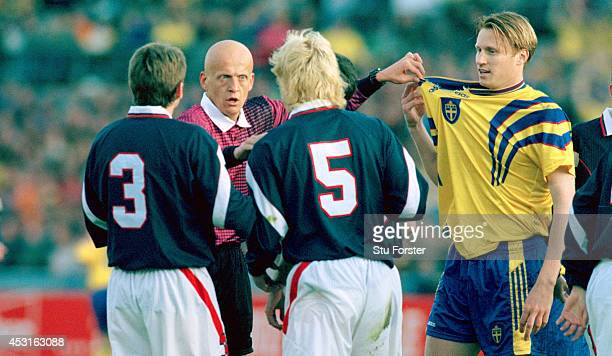 Referee Pierluigi Collina points out the ripped shirt of Sweden striker Kennet Andersson to Scotland defender Colin Hendry during a World Cup...