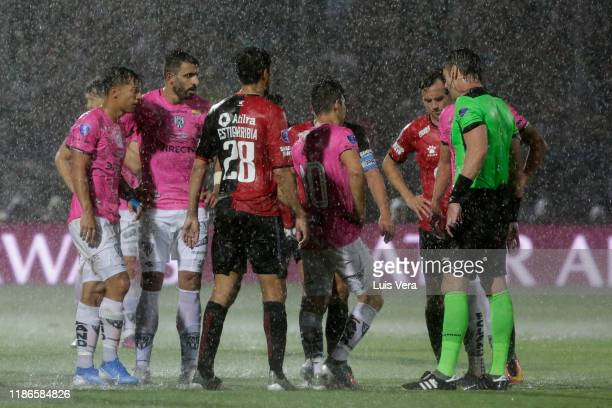 Referee Raphael Claus talks with players of Independiente del Valle and Colon on the possibility of stopping the match due to the heavy rain during...