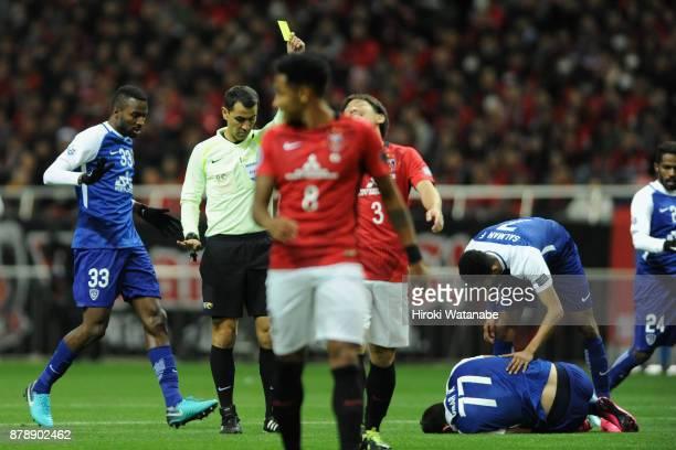referee Ravshan Irmatov is shown an yellow card to Tomoya Ugajin of Urawa Red Diamonds during the AFC Champions League Final second leg match between...