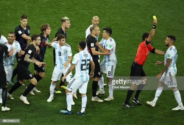 Referee Ravshan Irmatov shows Nicolas Otamendi of Argentina a yellow card as Croatia and Argentina players clash after Nicolas Otamendi of Argentina...