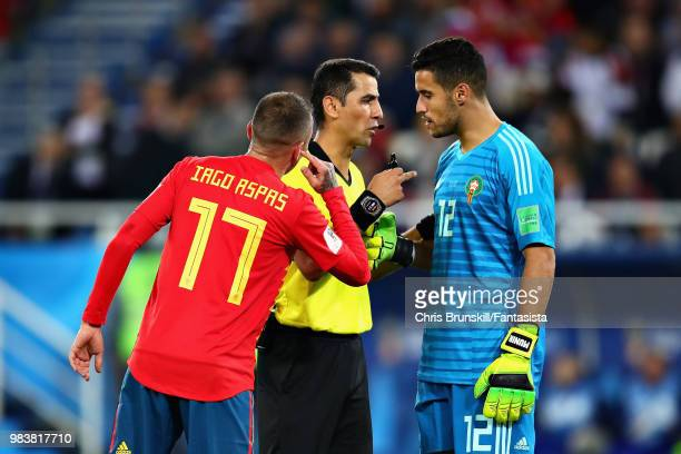 Referee Ravshan Irmatov talks with Munir Mohamedi of Morocco and Iago Aspas of Spain during the 2018 FIFA World Cup Russia group B match between...