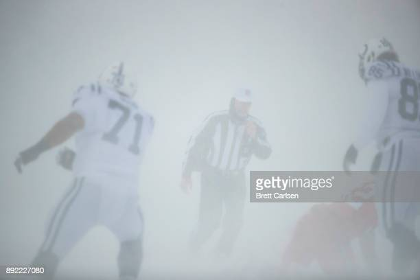 A referee reaches for his whistle during the heavy snows of the first half between the Buffalo Bills and the Indianapolis Colts at New Era Field on...