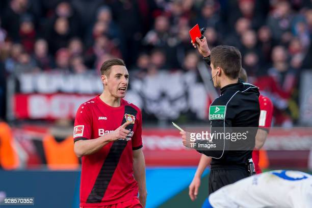 Referee Referee Daniel Siebert shows a yellow red card to Dominik Kohr of Leverkusen during the Bundesliga match between Bayer 04 Leverkusen and FC...