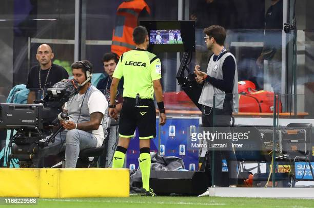 Referee reviews a play on the VAR during the Serie A match between FC Internazionale and Udinese Calcio at Stadio Giuseppe Meazza on September 14,...