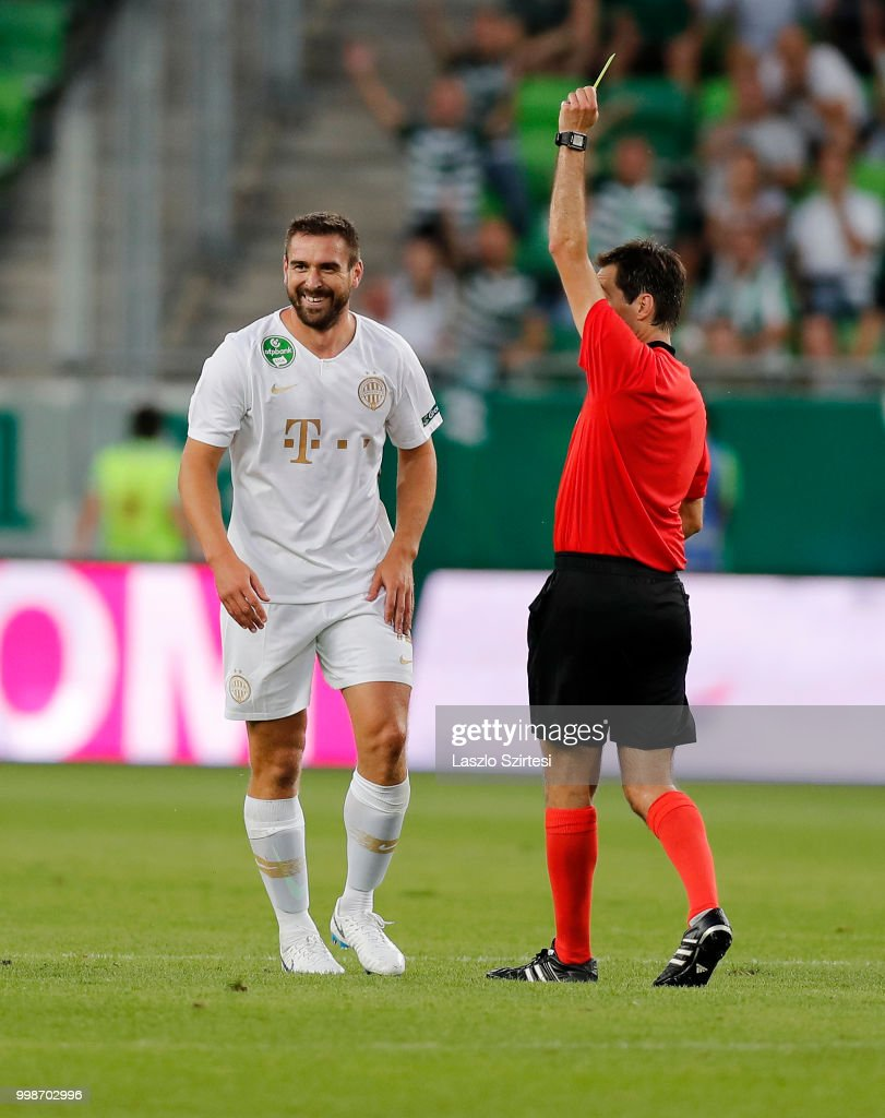 Referee Ricardo De Burgos shows the yellow card for Daniel Bode of Ferencvarosi TC during the UEFA Europa League First Qualifying Round 1st Leg match between Ferencvarosi TC and Maccabi Tel Aviv FC at Groupama Arena on July 12, 2018 in Budapest, Hungary.