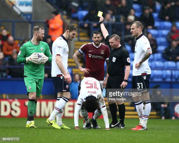 Referee Richard Smith shows a Yellow card to Marc Richards of Northampton Town after a foul on Derik Osede of Bolton Wanderers as his team mates Ben...