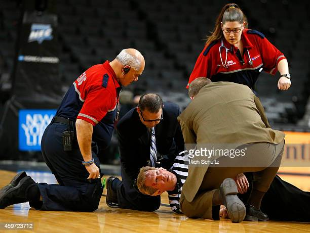 Referee Rick Crawford is attended to by EMS workers after collapsing on the floor just after the tip off of the consolation game between the La Salle...