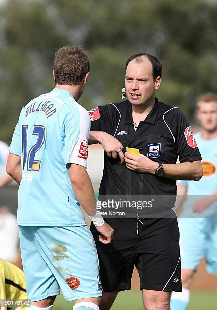 Referee Rob Shoebridge shows a yellow card to Ryan Gilligan of Northamppotn during the Coca Cola League Two Match between Burton Albion and...