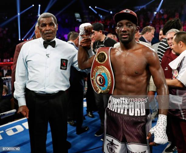 Referee Robert Byrd holds up the arm of Terence Crawford as he celebrates his ninthround TKO victory over Jeff Horn in their WBO welterweight title...