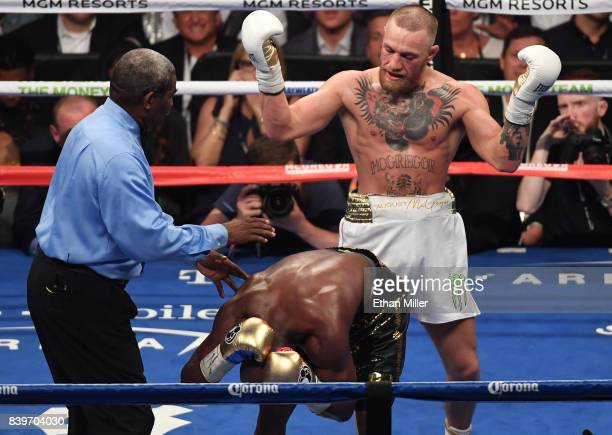 Referee Robert Byrd steps in as Floyd Mayweather Jr reacts to a punch in the back of the head from Conor McGregor in the eighth round of their super...