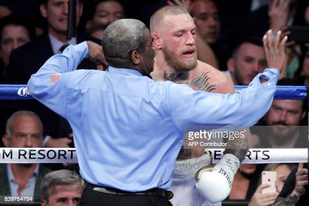 Referee Robert Byrd waves his arms in front of mixed martial arts star Conor McGregor as he stops the fight in the 10th round against boxer Floyd...