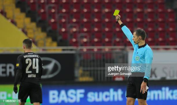 Referee Robert Hartmann displays yelow card for Julian Guttau of Halle n during the 3. Liga match between 1. FC Kaiserslautern and Hallescher FC at...