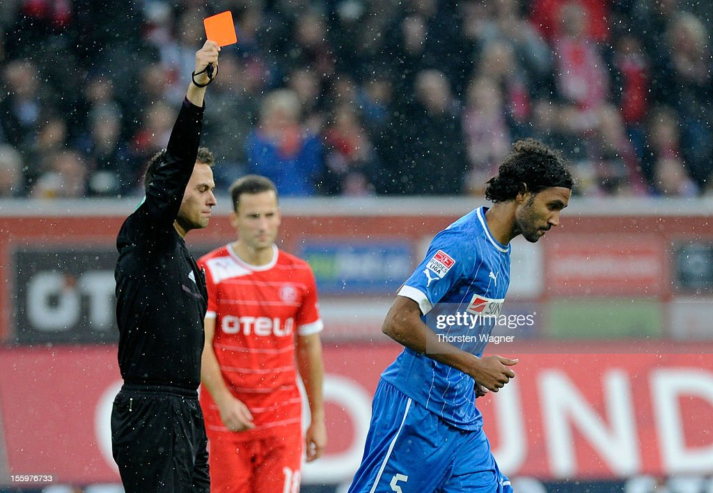 Referee Robert Hartmann (L) is showing the red card to Marvin Compper (R) of Hoffenheim during the Bundesliga march between Fortuna Duesseldorf and TSG 1899 Hoffenheim at Esprit-Arena on November 10, 2012 in Duesseldorf, Germany.