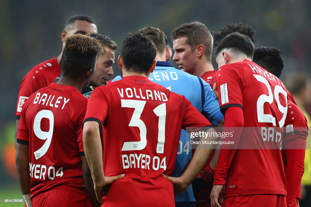 Referee Robert Hartmann is surround by players of Leverkusen after he sent off Wendell of Bayer Leverkusen (not seen) with a red card during the Bundesliga match between Bayer 04 Leverkusen and Borussia Dortmund at BayArena on December 2, 2017 in Leverkusen, Germany.