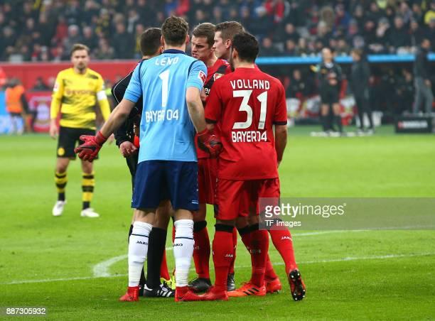 Referee Robert Hartmann speaks with Bernd Leno of Leverkusen Sven Bender of Leverkusen Lars Bender of Leverkusen and Kevin Volland of Leverkusen...