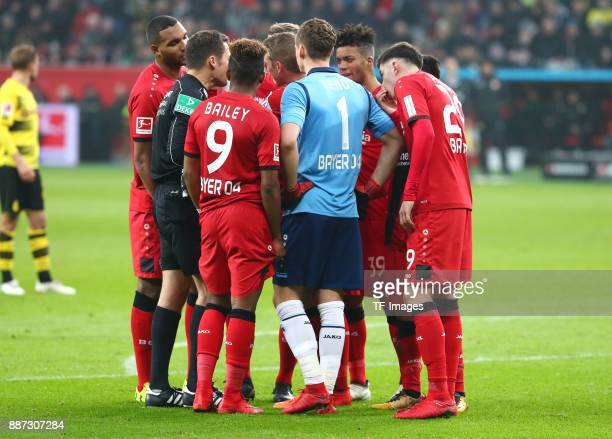 Referee Robert Hartmann speaks with Jonathan Tah of Leverkusen Leon Bailey of Leverkusen Bernd Leno of Leverkusen Benjamin Henrichs of Leverkusen and...