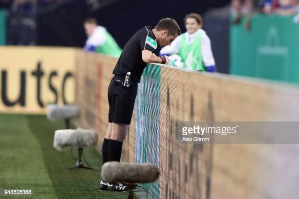 Referee Robert Hartmann takes a look at the VAR screen before showing the red card to Gelson Fernandes of Frankfurt during the DFB Cup Semi Final...