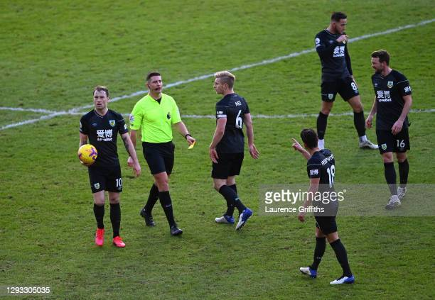 Referee Robert Jones gives a yellow card to Ashley Westwood of Burnley as Ashley Barnes, Ben Mee and Chris Wood look on during the Premier League...