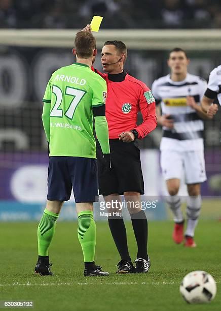 Referee Robert Kampka shows the yellow card to Maximilian Arnold of Wolfsburg during the Bundesliga match between Borussia Moenchengladbach and VfL...