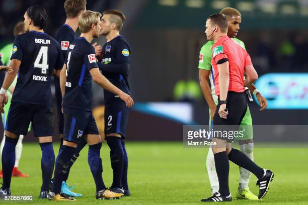 Referee Robert Kampka takes back a goal from Yunus Malli of Wolfsburg following a video assistant referee decision during the Bundesliga match...