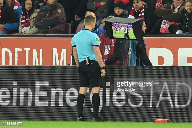 Referee Robert Kampka uses the VAR screen to make a decision regarding a penalty in favour of TSG 1899 Hoffenheim during the Bundesliga match between...