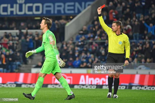 Referee Robert Kempter shows the yellowred card to goalkeeper Manuel Riemann of Bochum during the Second Bundesliga match between DSC Arminia...