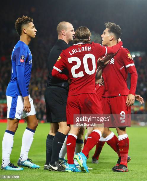 Referee Robert Madley and Adam Lallana of Liverpool intervene as Mason Holgate of Everton and Roberto Firmino of Liverpool clash during the Emirates...