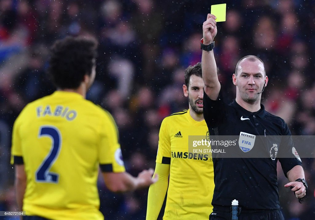 Referee Robert Madley (R) shows a yellow card to Middlesbrough's Brazilian defender Fabio for his challenge on Crystal Palace's Ivorian-born English striker Wilfried Zaha during the English Premier League football match between Crystal Palace and Middlesbrough at Selhurst Park in south London on February 25, 2017. / AFP PHOTO / Ben STANSALL / RESTRICTED TO EDITORIAL USE. No use with unauthorized audio, video, data, fixture lists, club/league logos or 'live' services. Online in-match use limited to 75 images, no video emulation. No use in betting, games or single club/league/player publications. /