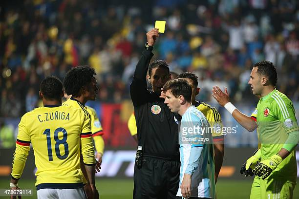 Referee Roberto Garcia shows a yellow card to Lionel Messi of Argentina during the 2015 Copa America Chile quarter final match between Argentina and...