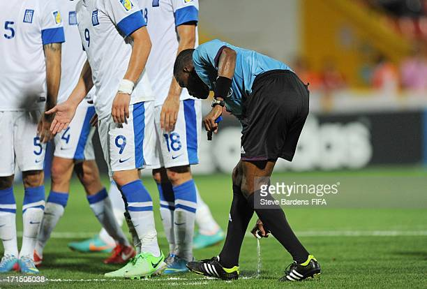 Referee Roberto Moreno of Panama sprays a foam marker line onto the pitch to illustrate where a Greek defensive wall must stand during the FIFA U20...