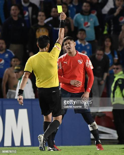 Referee Roberto Tobar shows the yellow card to Alan Franco of Independiente during a match between Millonarios and Independiente as part of Copa...