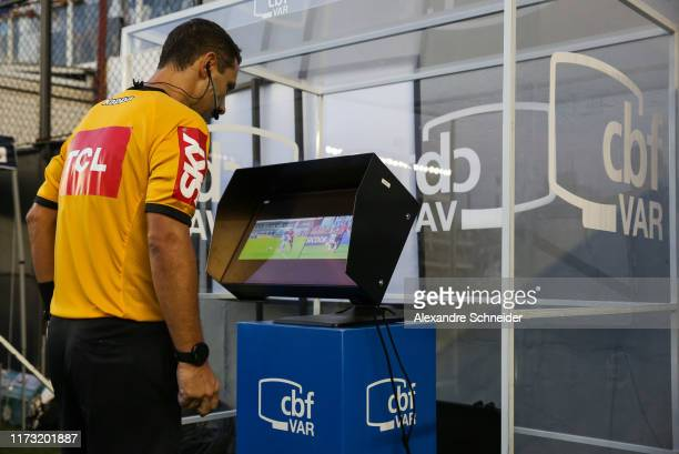 Referee Rodrigo Cavalhaes de Miranda checks the VAR and calls a penalty for Santos during the match for the Brasileirao Series A 2019 at Vila Belmiro...