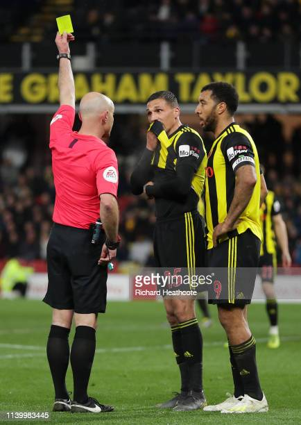 Referee Roger East shows Jose Holebas of Watford a yellow card during the Premier League match between Watford FC and Fulham FC at Vicarage Road on...