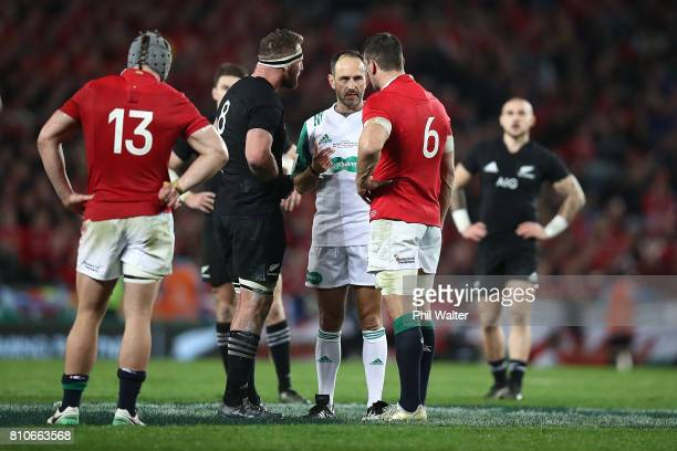 Referee Romain Poite speaks with All Black captain Kieran Read and Lions captain Sam Warburton as he downgrades a call made in the final minutes from...
