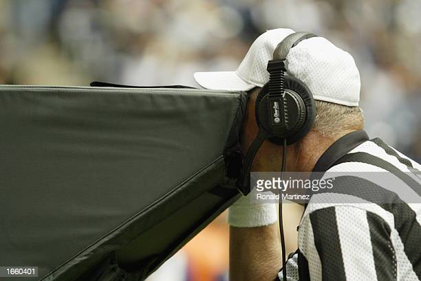 Referee Ron Blum examines a replay challenge during the NFL game between the Carolina Panthers and the Dallas Cowboys at Texas Stadium on October 13...