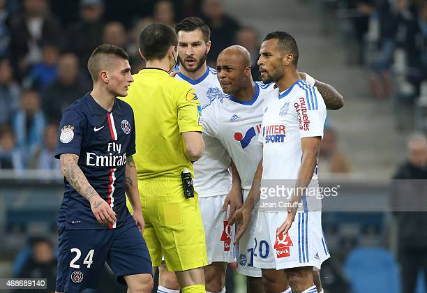 Referee Ruddy Buquet argues with AndrePierre Gignac Andre Ayew and JacquesAlaixys Romao of OM during the French Ligue 1 match between Olympique de...