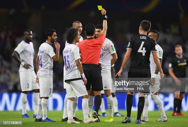 Referee Ryuji Sato shows a yellow card to Mohanad Salem of Al Ain during the FIFA Club World Cup first round playoff match between Al Ain FC and Team...