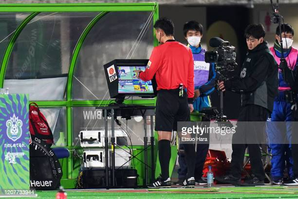 Referee Ryuji Sato watches VAR monitor and points the scene of the penalty during the J.League MEIJI YASUDA J1 match between Shonan Bellmare and...