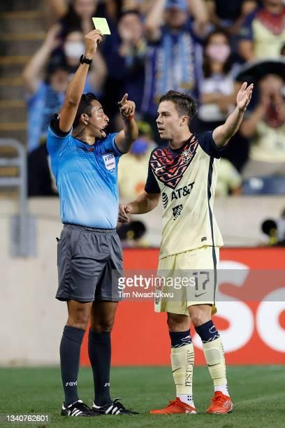 Referee Said Martinez issues a yellow card to Sebastián Córdova of Club America during the semifinal second leg match between Philadelphia Union and...