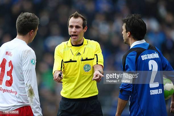 Referee Sascha Stegemann argues with Jim - Patrick Mueller of Regensburg and Markus Schuler of Bielefeld during the Third League match between...