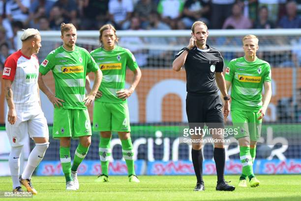 Referee Sascha Stegemann checks with the video referee if the first goal was correct, during the Bundesliga match between FC Augsburg and Borussia...