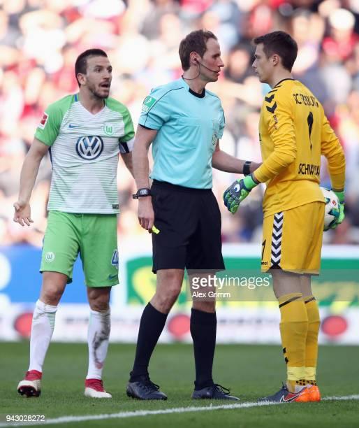 Referee Sascha Stegemann discusses with goalkeeper Alexander Schwolow of Freiburg and Ignacio Camacho of Wolfsburg during the Bundesliga match...