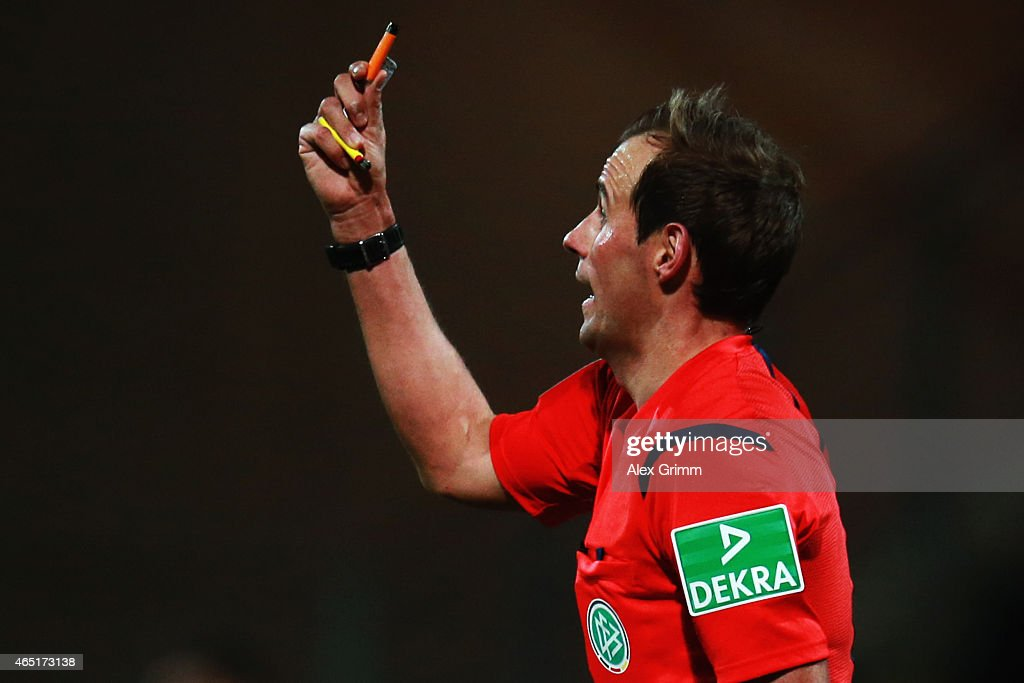 Referee Sascha Stegemann holds up lighters during the DFB Cup Round of 16 match between VfR Aalen and 1899 Hoffenheim at Scholz Arena on March 3, 2015 in Aalen, Germany.