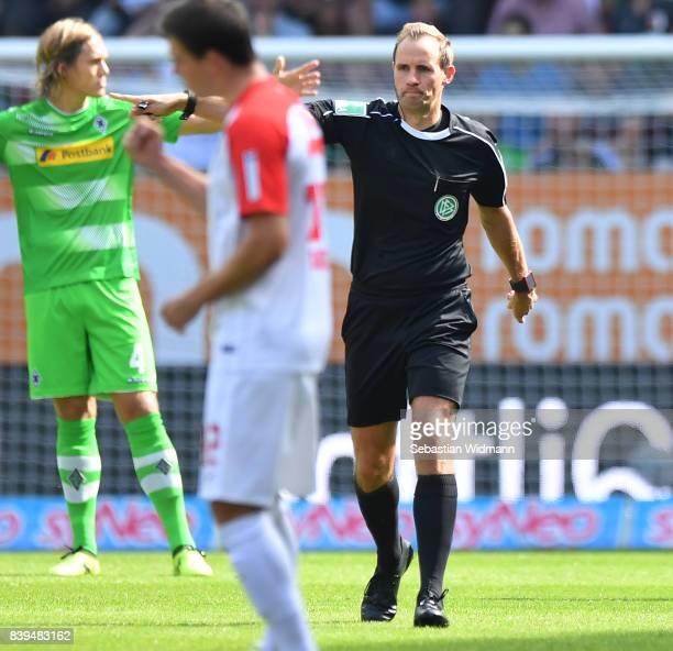 Referee Sascha Stegemann proves the first goal after he checked with the video referee, during the Bundesliga match between FC Augsburg and Borussia...