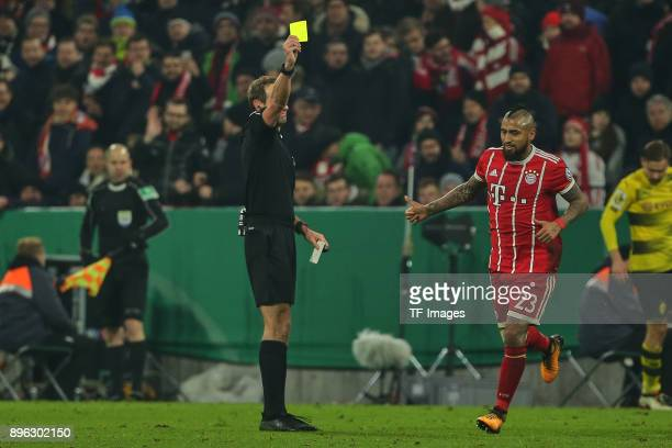 Referee Sascha Stegemann shows a yellow card to Arturo Vidal of Muenchen during the DFB Cup match between Bayern Muenchen and Borussia Dortmund at...